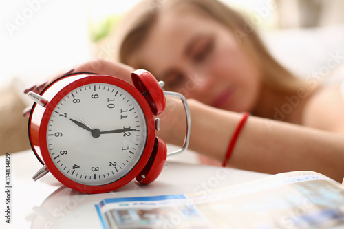 Obraz A young woman can not wake up at 7 am to work after a tumultuous party under the alarm clock - fototapety do salonu