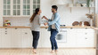 canvas print picture - Happy family couple dancing barefoot on wooden floor in kitchen.