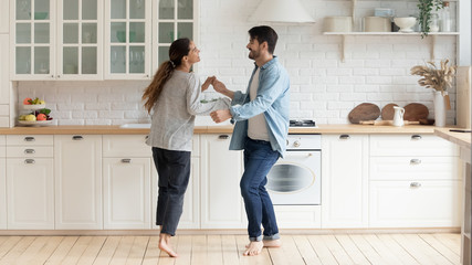 Happy family couple dancing barefoot on wooden floor in kitchen.