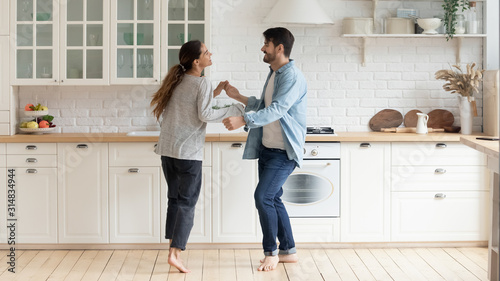 Happy family couple dancing barefoot on wooden floor in kitchen. - 314834944