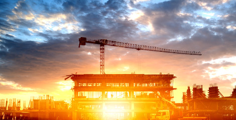 Silhouette of a building with a construction crane against the clouds