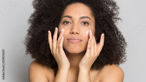 Photo Young african american woman applying professional skincare product