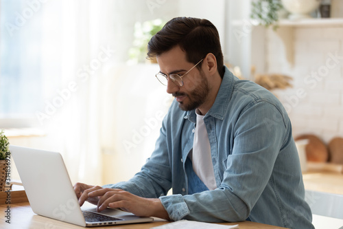 Handsome young businessman in eyewear working with computer remotely.
