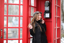 Beautiful Young Girl In A Phone Booth. The Girl Is Talking On The Phone From The Payphone. English Telephone Booth In The Street And A Woman Talking On Phone.