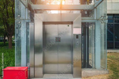 Modern elevator or lift with closed metal door in public park