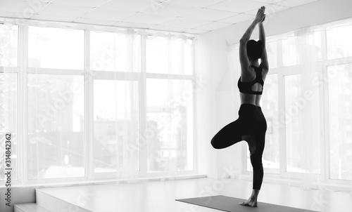 Fotografia Sporty woman practicing yoga in tree pose