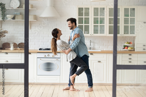 Full length handsome young man embracing and dropping smiling wife.