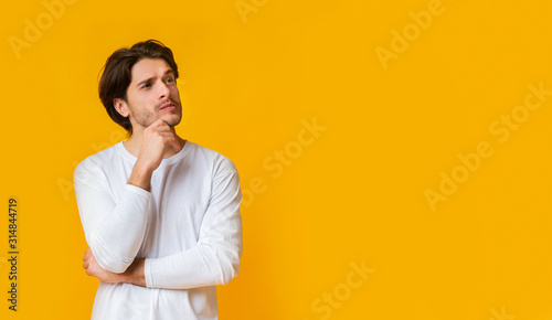 Fotografía Doubtful man thinking about something, touching chin with thoughtful face expres