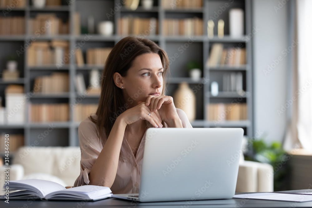 Fototapeta Pensive young woman distracted from work thinking