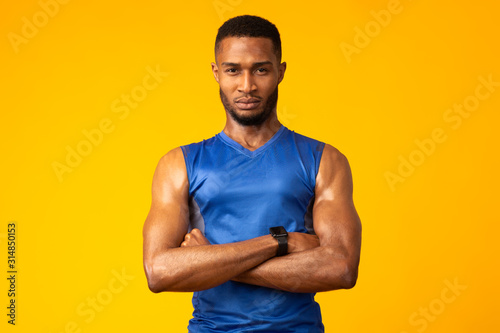 Obraz na plátne Afro sportsman with folded arms at studio