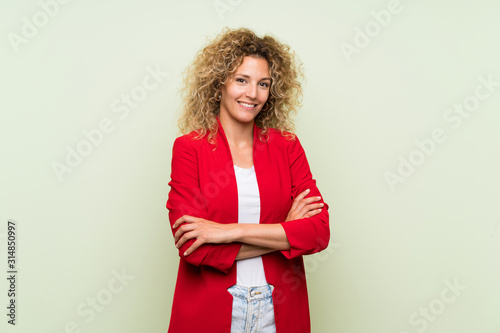 Young blonde woman with curly hair over isolated green background keeping the ar Canvas Print
