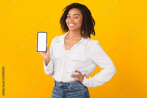 Fotomural Smiling afro woman showing new app on phone