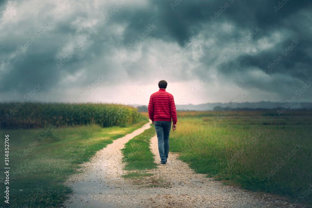Fototapeta Man in red jacket walks alone on rural road with dark cloudy sky.