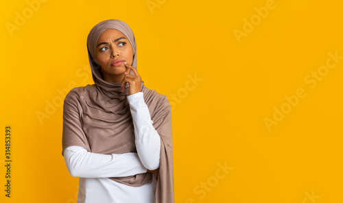 Portrait of doubtful afro islamic girl in headscarf over yellow background