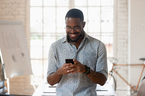 Smiling biracial male employee using cellphone in office boardroom Wallpaper Mural