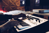 male musician hands playing keyboard synthesizer in recording studio
