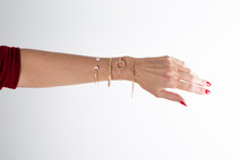 Woman Arm Hands With Gold Bracelets In White Background