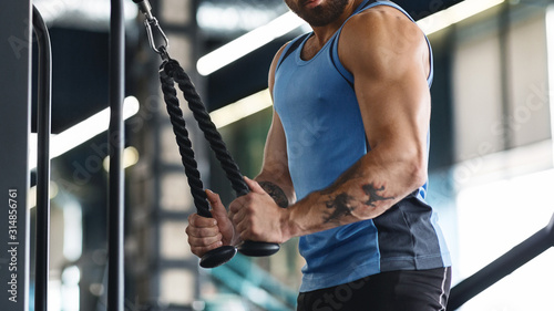 Photo Muscular guy exercising with training apparatus at gym