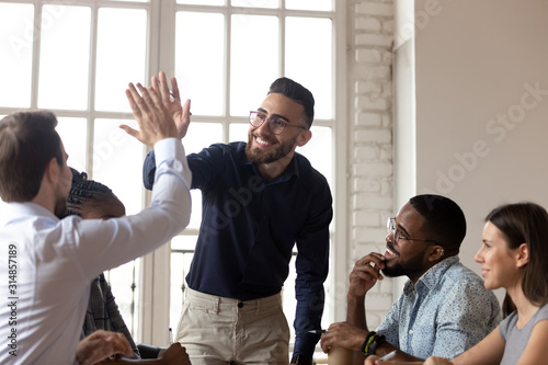 Smiling multiethnic male colleagues celebrate shared success Tableau sur Toile