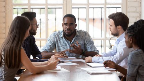 Multinational millennial colleagues gather at office meeting Canvas Print