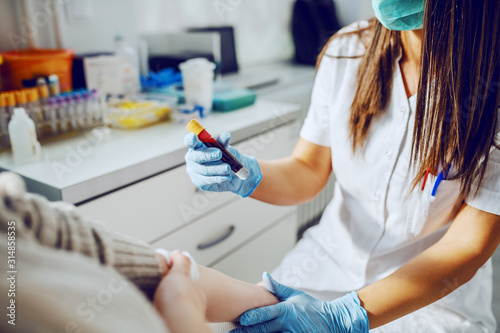 Photo Caucasian laboratory assistant in uniform, with mask and rubber gloves holding test tube with blood while patient sitting and holding absorbent cotton