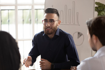 Confident Arabic businessman hold team meeting with employees