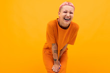 Girl With Pink Hair And A Pierced Face Dressed In A Loose Orange Dress On A Yellow Background