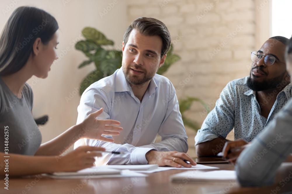 Fototapeta Diverse businesspeople talk discussing ideas at team meeting