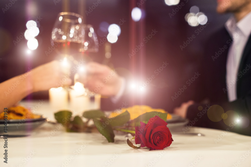 Fototapeta Romantic couple toasting with red wine during candlelight dinner