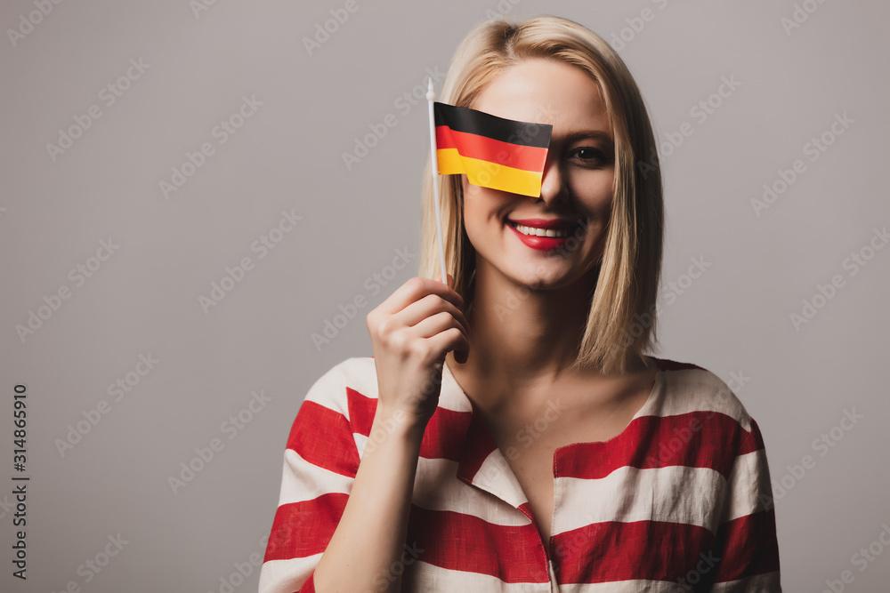 Fototapeta beatiful girl holds German flag on gray background