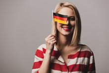 Beatiful Girl Holds German Flag On Gray Background