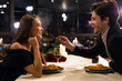canvas print picture - Cheerful man feeding his girlfriend on romantic date