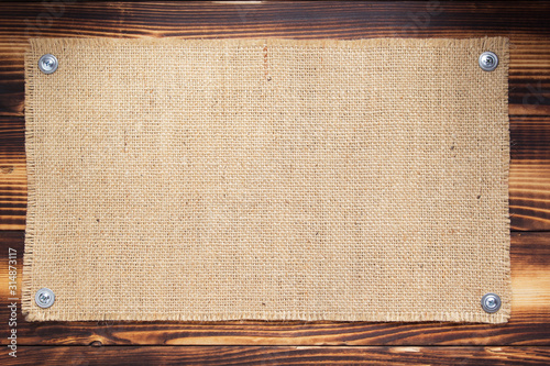burlap hessian sacking texture on wooden background Canvas Print