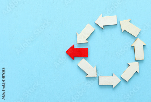 Fotografía  Concept image of red arrow facing opposite direction from other arrows in group