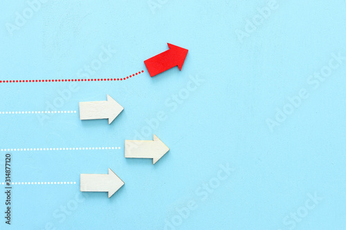 Photo Concept image of red arrow facing opposite direction from other arrows in group