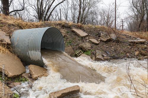 Obraz na plátne Closeup motion blur of storm water runoff flowing through metal drainage culvert under road