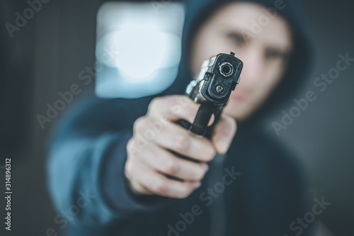 Fotografie, Obraz Crime or robbery concept: Man with black gun is aiming with his weapon