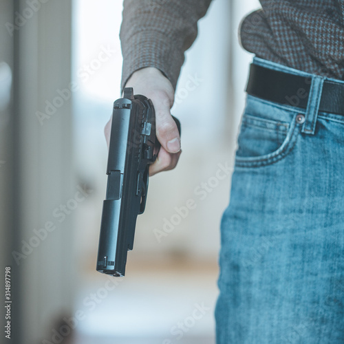 Police undercover weapon concept: Man is holding black weapon in his hand Wallpaper Mural