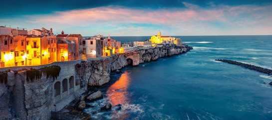 Obraz na Szkle Miasta Dramatic evening cityscape of Vieste - coastal town in Gargano National Park, Italy, Europe. Splendid spring sunset on Adriatic sea. Traveling concept background.