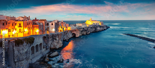 Dramatic evening cityscape of Vieste - coastal town in Gargano National Park, Italy, Europe. Splendid spring sunset on Adriatic sea. Traveling concept background.