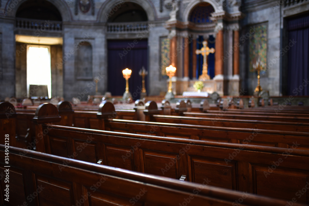 Fototapeta Interior of Catholic church with selective focus on benches