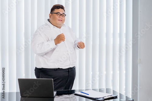 Fat businessman cheering and dancing for his work Canvas Print