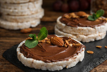 Puffed Rice Cakes With Chocolate Spread, Nuts And Mint On Wooden Table, Closeup