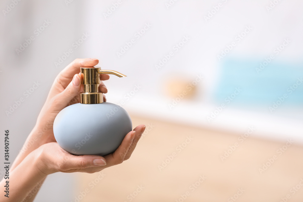 Fototapeta Woman holding soap dispenser on blurred background, closeup. Space for text