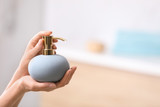 Fototapeta Kawa jest smaczna - Woman holding soap dispenser on blurred background, closeup. Space for text