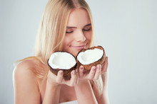 Beautiful Young Girl With Bare Shoulders Holds A Coconut In Her Hands. Skin Care Concept, Spa Salon