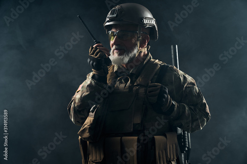 Old military commander holding radio station. Fotobehang
