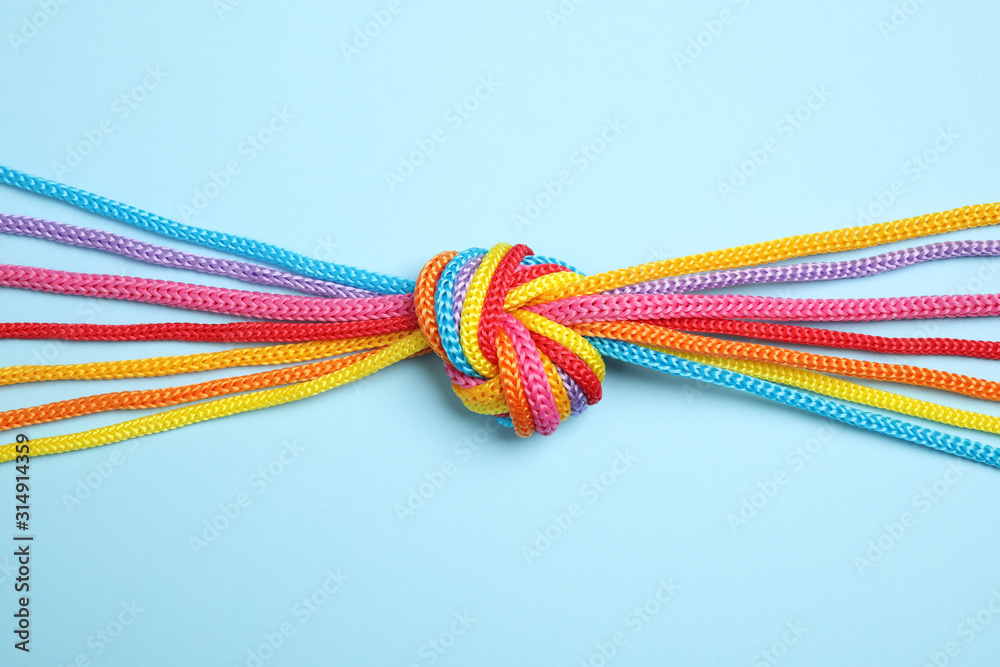 Fototapeta Colorful ropes tied together on light blue background, top view. Unity concept