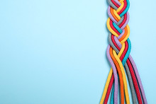 Top View Of Braided Colorful Ropes On Light Blue Background, Space For Text. Unity Concept