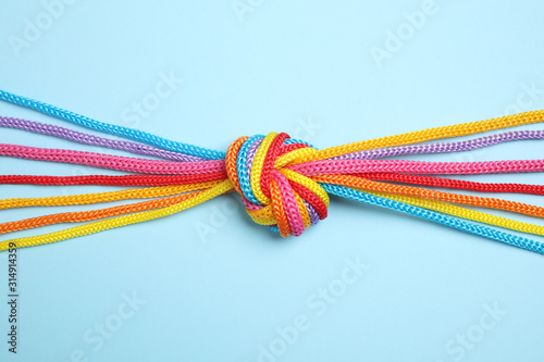Obraz Colorful ropes tied together on light blue background, top view. Unity concept - fototapety do salonu
